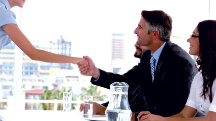 Business people on interview panel shaking hands with applicant