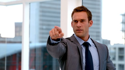 Stern handsome businessman pointing ahead