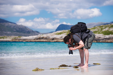 Photographer at a sunny white sand beach, Scotland.
