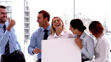Team of business people laughing together with card