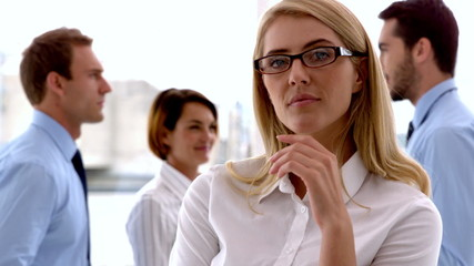 Businesswoman looking at camera with colleagues behind her