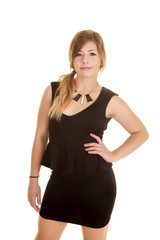 woman black dress with hand on hip small smile