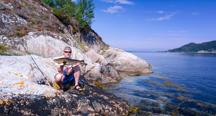 Happy angler with big cod in amazing scenery