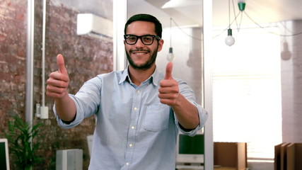 Casual businessman showing thumbs up to camera