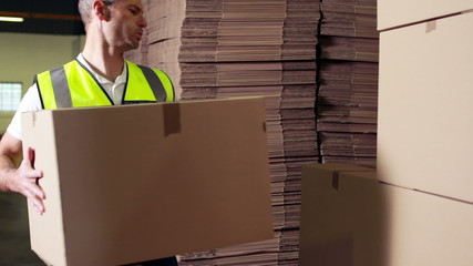 Warehouse worker stacking cardboard boxes