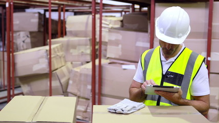 Warehouse worker checking boxes for shipping with tablet pc
