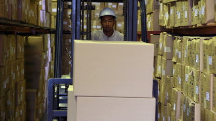 Forklift driver picking up palette of boxes