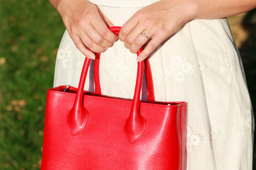 Newly engaged woman holding red leather bag