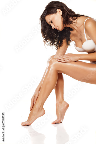 canvas print picture beautiful young woman apply lotion on her legs