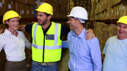 Warehouse team smiling and high fiving each other