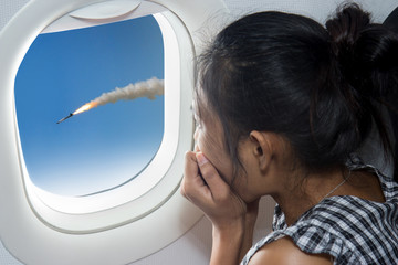 woman watching a rocket from an airplane window