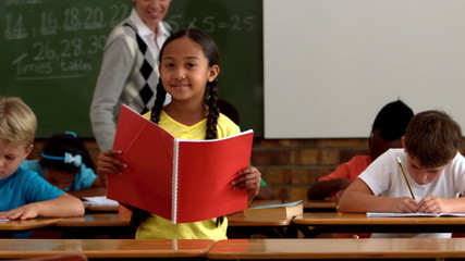 Little girl holding red notepad smiling at camera in classroom