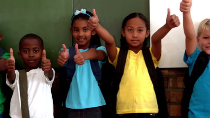 Cute pupils showing thumbs up in classroom
