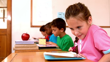 Cute little girl reading book in the classroom