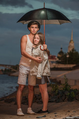 The guy and the girl under a umbrella