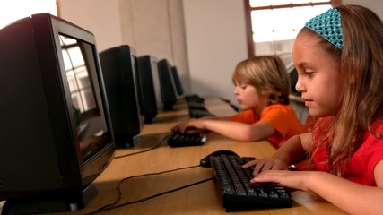 Cute pupils working on computers in classroom
