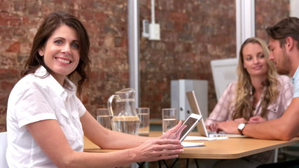 Casual businesswoman smiling at camera using tablet pc