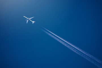 Airliner at high altitude with white condesation trails