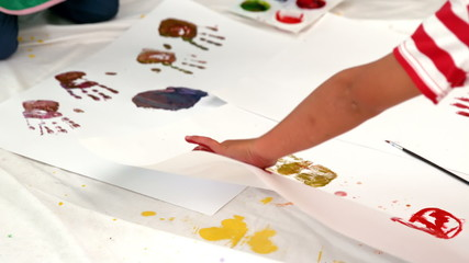 Cute little boys painting lying on paper in classroom