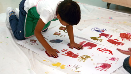 Cute little boys painting with hands lying on paper in classroom