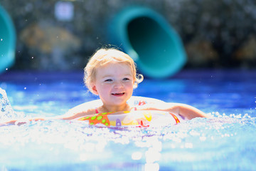 Happy little girl swimming in outdoors pool with inflatable ring