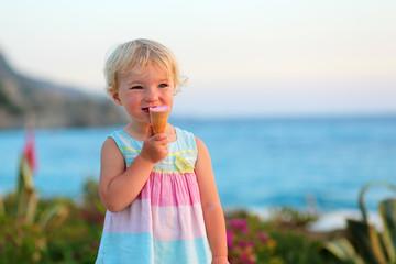 Little girl eating ice cream walking on beautiful promenade