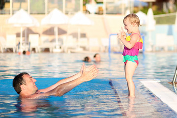 Father and daughter having fun in outdoors swimming pool