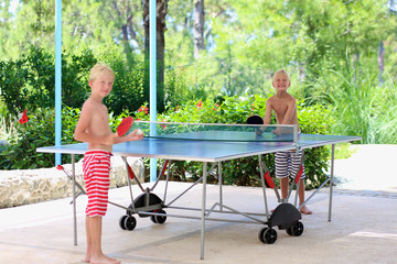 Two happy boys playing ping pong outdoors