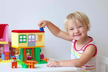 Happy preschooler girl building house from plastic blocks