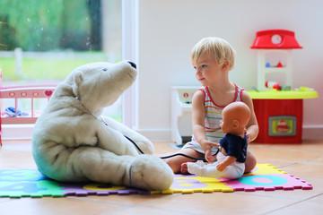 Little girl plays doctor providing healthcare to teddy bear