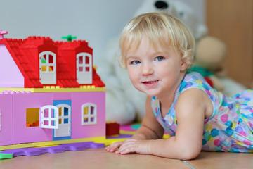 Happy preschooler girl building house from plastic blocks