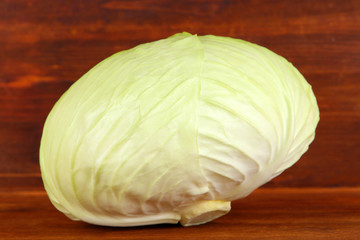 Whole green cabbage on wooden background
