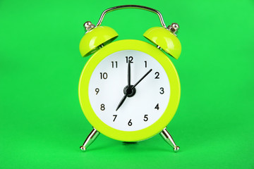 Light green alarm clock on green background
