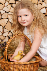 Cute little girl with duckling has easter