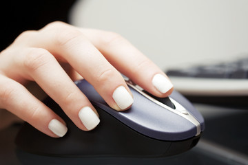 Female hands using computer mouse