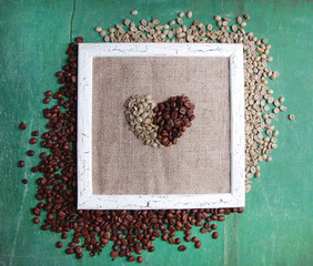 Wooden frame and coffee grains on wooden background