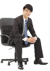 smiling and handsome Young business man sitting on a chair