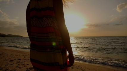 Young Woman Playing with Her Curly Hairs on Beach at Sunset in