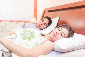 latin couple lying in bed sleeping