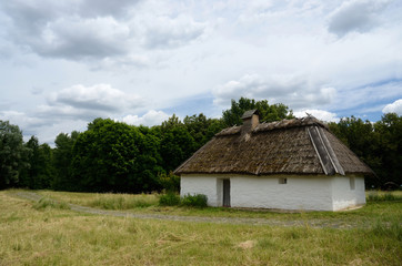 Antique white clay house with hay roof in Pirogovo park, Kiev
