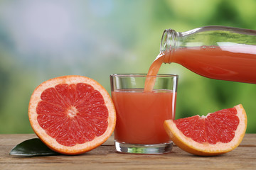 Grapefruitsaft eingießen aus frischer Grapefruit im Sommer