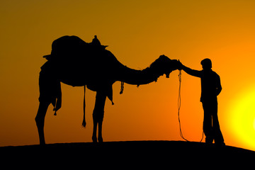 Silhouette man and camel at sunset in the desert, India