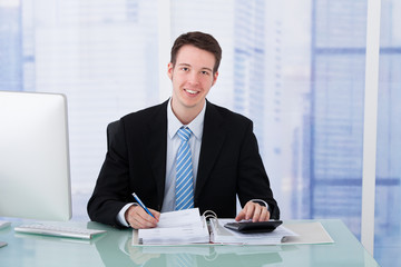 Confident Businessman Using Calculator At Office Desk