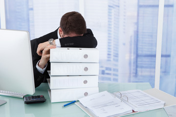 Stressed Businessman Resting Head On Binders At Desk