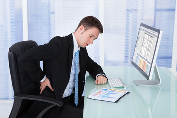 Businessman Suffering From Backache At Computer Desk