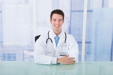 Confident Doctor Sitting At Desk In Clinic