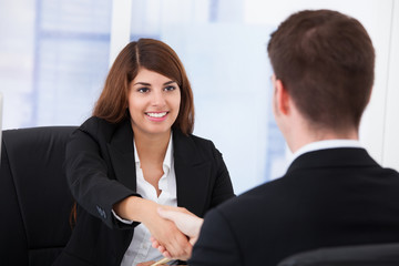 Businesswoman Shaking Hands With Partner In Office