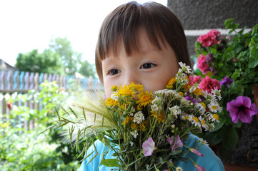 Boy behind the  summer bouquet of wildflowers