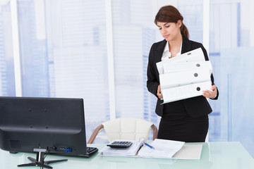 Businesswoman Carrying Binders In Office