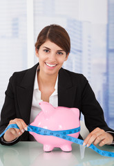 Confident Businesswoman Measuring Piggybank At Desk